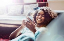 A young women reclines on a couch and smiles at the phone in her hand.
