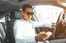 A man wearing sunglasses drives his car.
